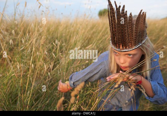 Girl hiding in long grass dressed up as a native american - Stock Image
