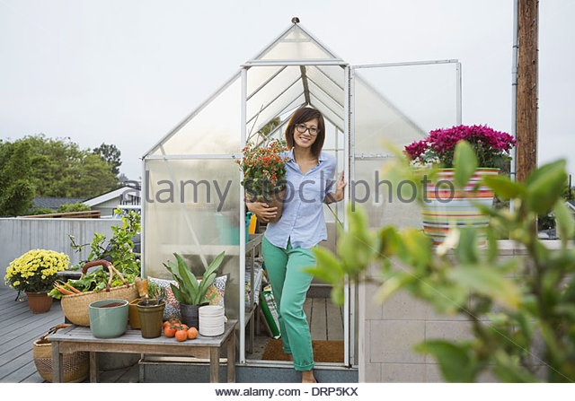Confident woman holding potted plant in greenhouse - Stock Image