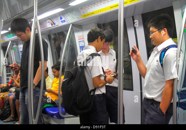 Singapore Farrer Road MRT Station Circle Line subway train public transportation riders commuters Asian teen boy - Stock Image