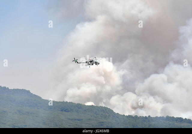 Torre del Greco-Naples, Italy. 11th Jul, 2017. Vesuvius Volcano forest fire Helicopter drops bucket of water Torre - Stock Image