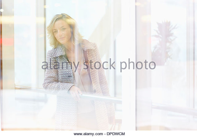 Mid adult woman peering through shopping centre window - Stock Image