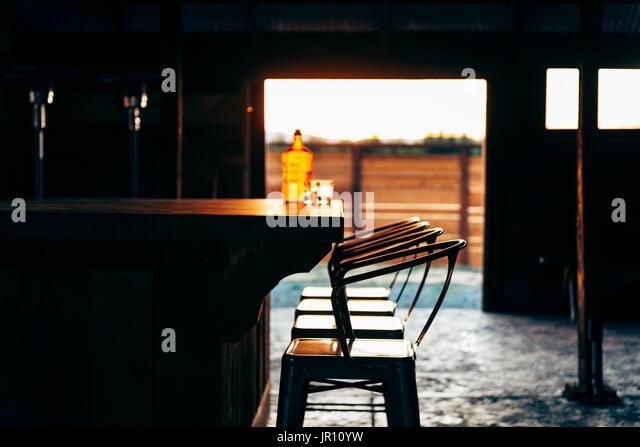 bar inside a barn, rustic bar, sun set - Stock Image