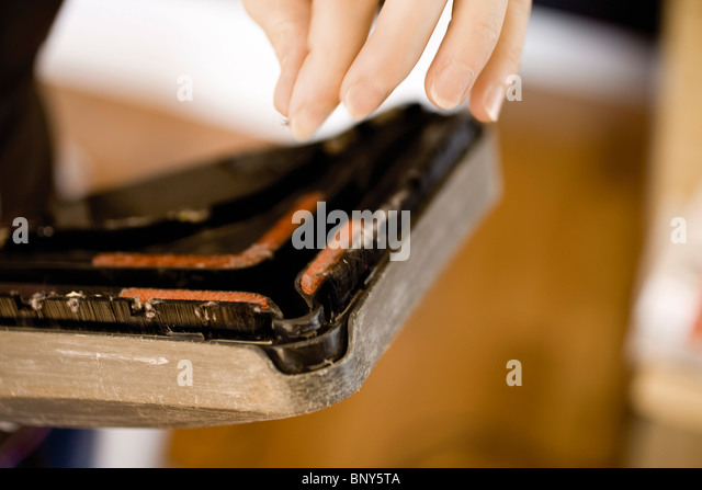 Removing lint from clogged vacuum cleaner - Stock Image
