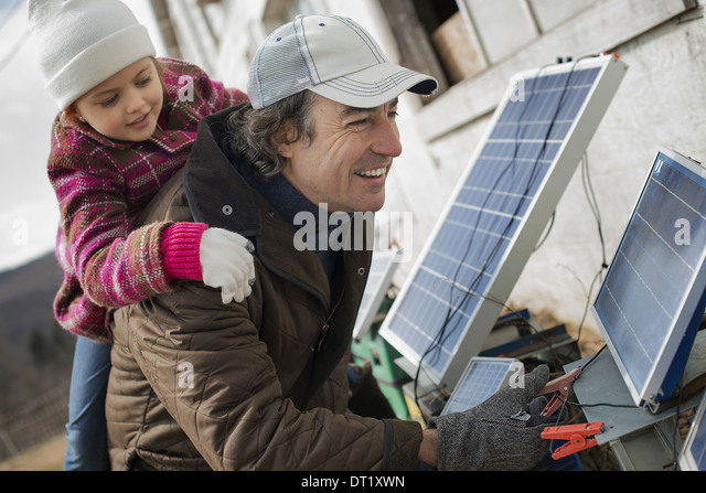 A man giving a child a piggybank while trying to connect the leads for solar power panels - Stock Image