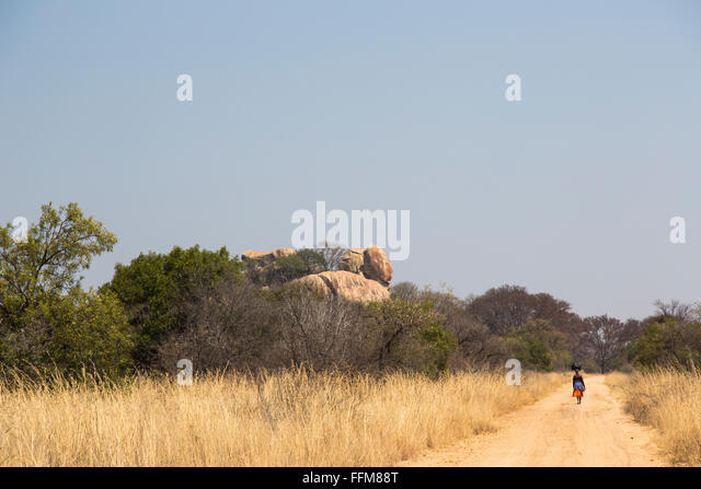 A local woman with a package balancing on her head walking down a rural dirt road in Western Zimbabwe - Stock Image