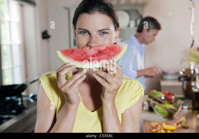 Germany, Hamburg, Couple in kitchen, woman holding melon slice - Stock Image