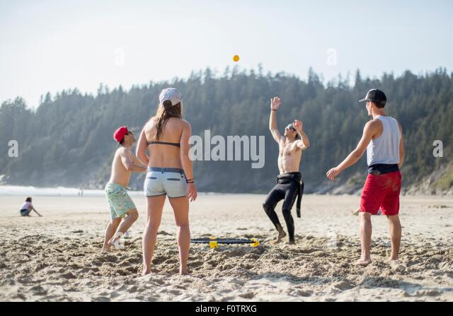 Four adult friends throwing and catching ball on Short Sands Beach, Oregon, USA - Stock Image