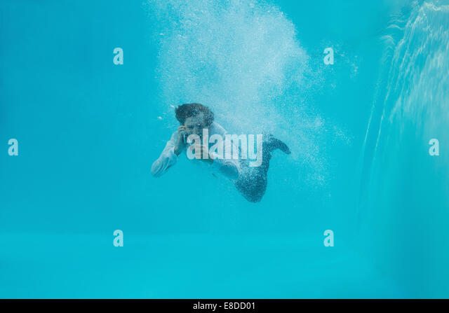 Young man swimming underwater - Stock Image