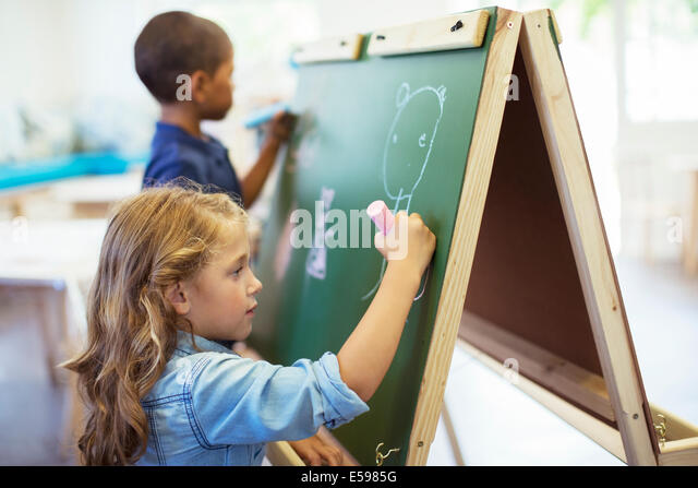 Students drawing on chalkboard in classroom - Stock-Bilder