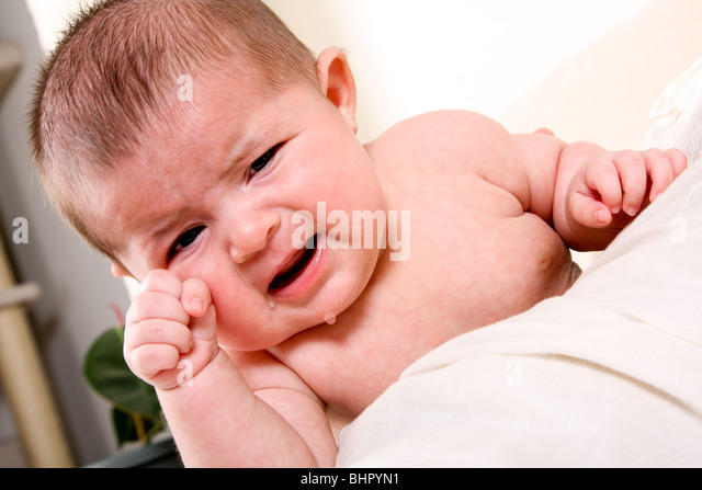 Face of an unhappy unisex Caucasian Hispanic baby crying with tears while rubbing eye. - Stock Image