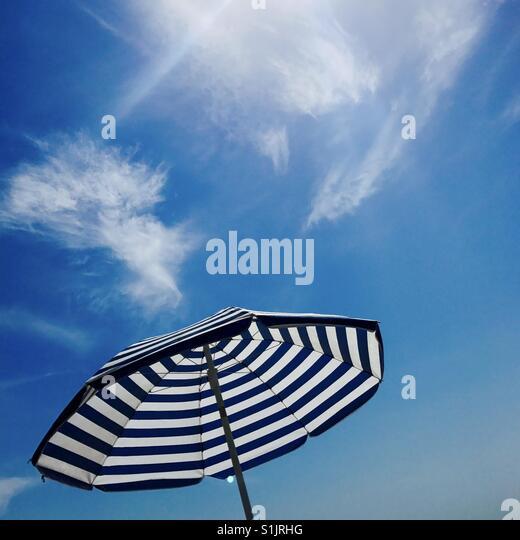 An umbrella and blue sky. Manhattan Beach, California USA. - Stock Image