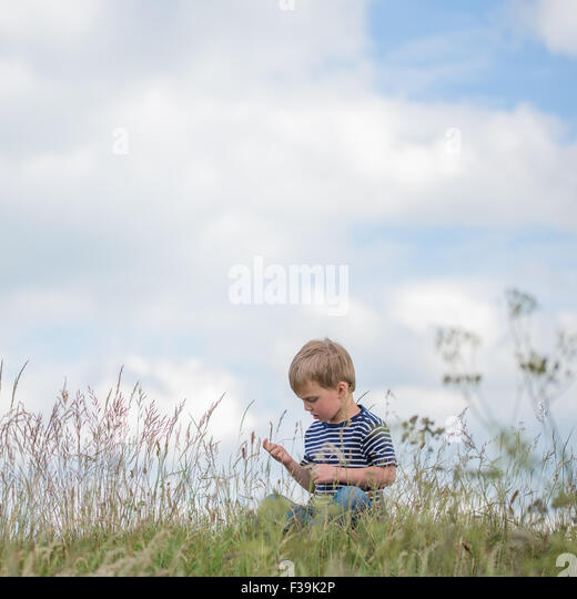 Boy sitting in long grass - Stock Image