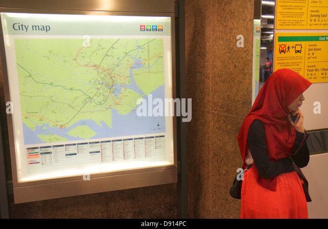 Singapore City Hall MRT Station East West Line subway train public transportation Asian woman Muslim route map hijab - Stock Image