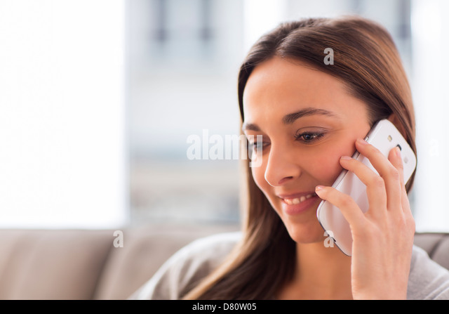 Pretty young woman using white mobile phone at home - Stock Image