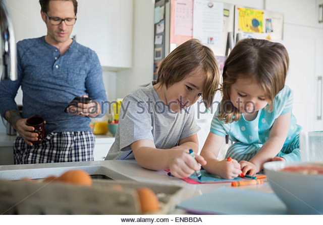 Father texting while children color in morning kitchen - Stock Image