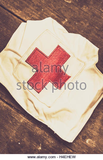 Antique white nursesl hat with red cross emblem against a wooden background - Stock Image