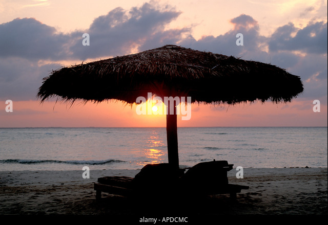 Mexico beach palapa thatch beach at sunset over calm Caribbean coast on the Riviera Maya - Stock Image
