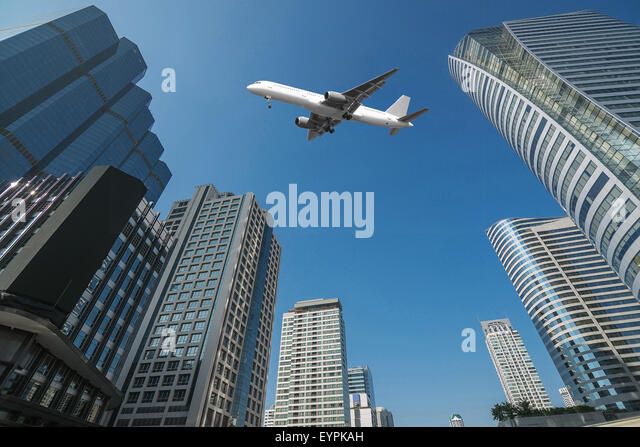 Shot of airplane flying above skyscrapers in City of Bangkok downtown - Stock Image