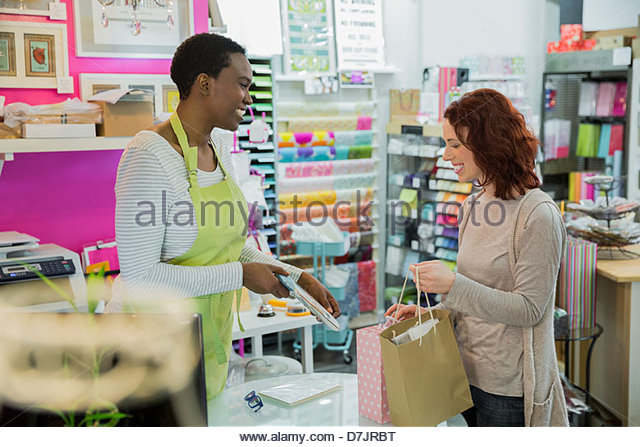Female small business owner showing options to customer - Stock Image