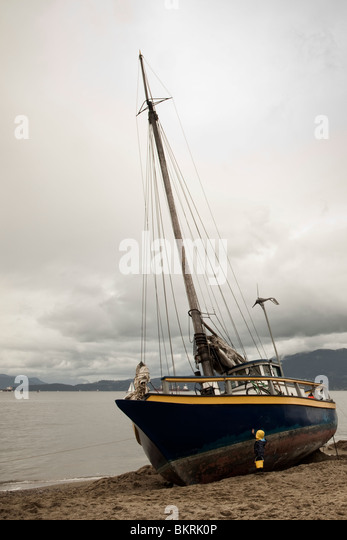 A small boy reaches to touch the hull of a sailboat that is beached on Kitsilano beach in Vancouver, British Columbia, - Stock Image