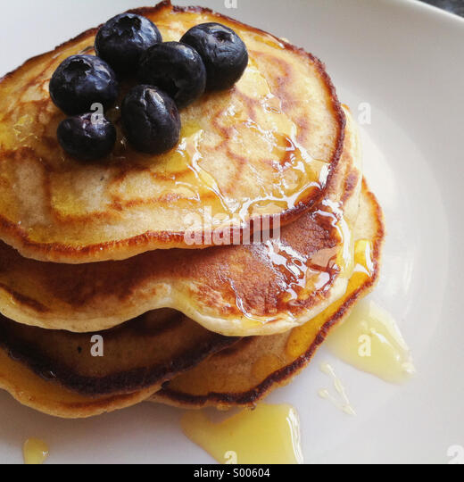 American pancakes topped with syrup and blueberries - Stock-Bilder