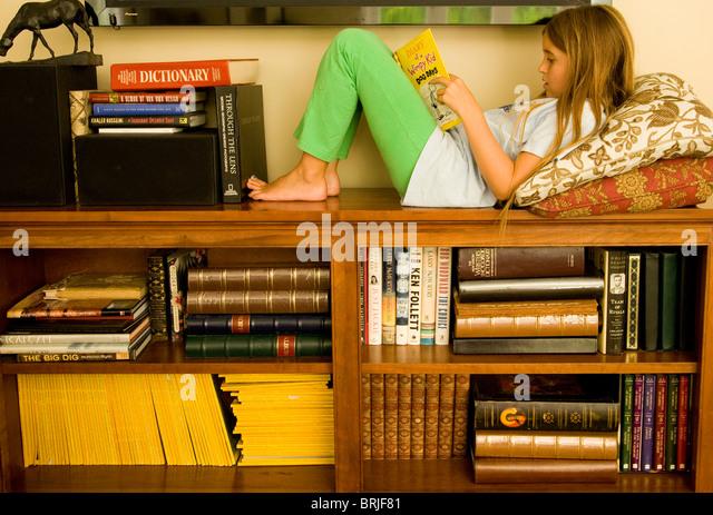 Girl on bookshelf reading a book - Stock Image