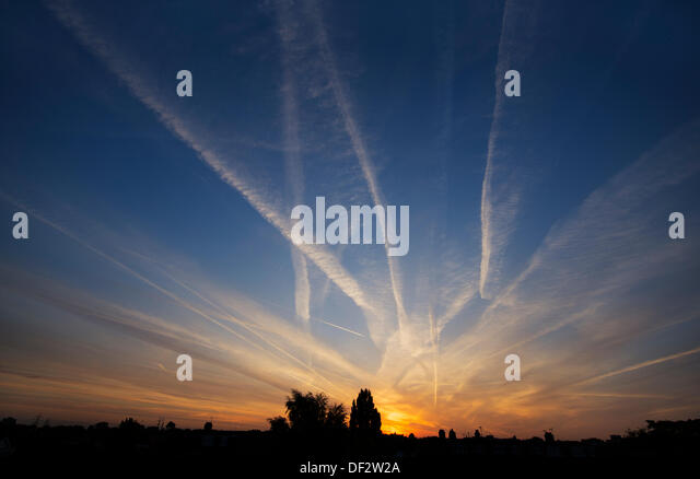 London, UK. 27th Sep, 2013. Vapour trails from passing high altitude aircraft fill the early morning sky at sunrise - Stock Image