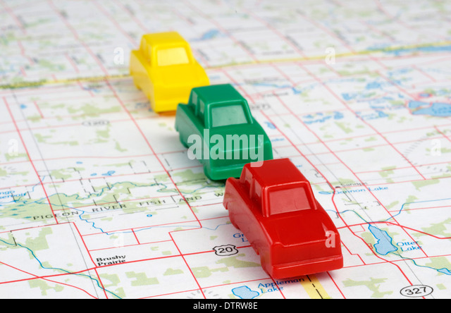 Red,green,yellow miniature cars are traveling forward on a map. - Stock Image