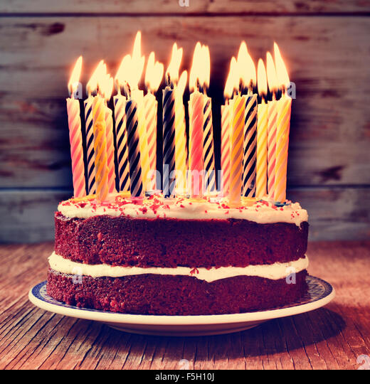 a cake topped with some lit candles before blowing out the cake, on a rustic wooden table, with a filtered effect - Stock Image