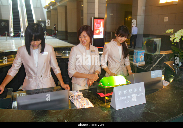 China Hong Kong Island Admiralty Bank of China Tower lobby visitor registration desk Asian woman receptionist coworkers - Stock Image