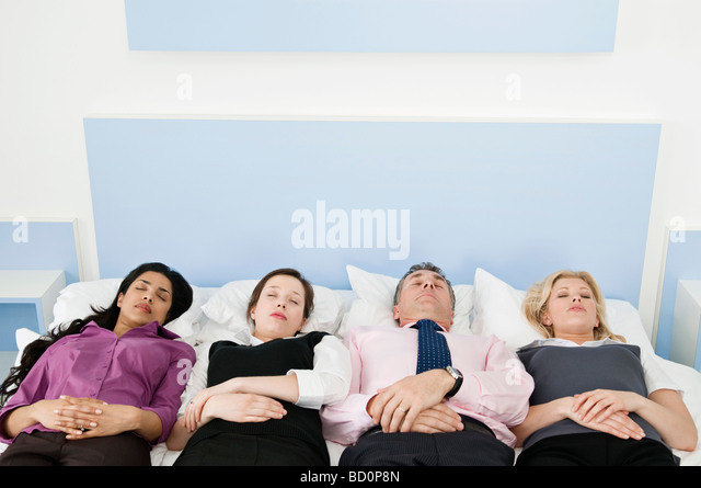 Four business people in a bed - Stock Image