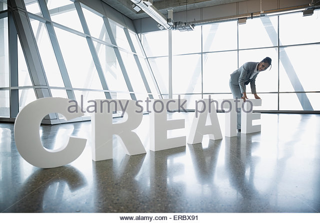 Businesswoman straightening 'Creative' letters - Stock Image