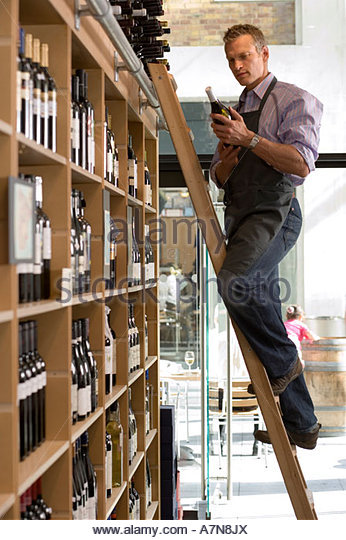 Shop owner looking at bottle of wine in off licence standing on step ladder beside shelf side view - Stock Image
