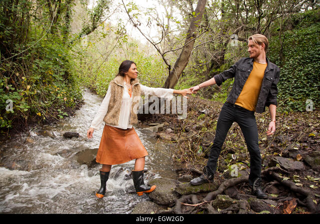 Woman helping man across creek. - Stock-Bilder