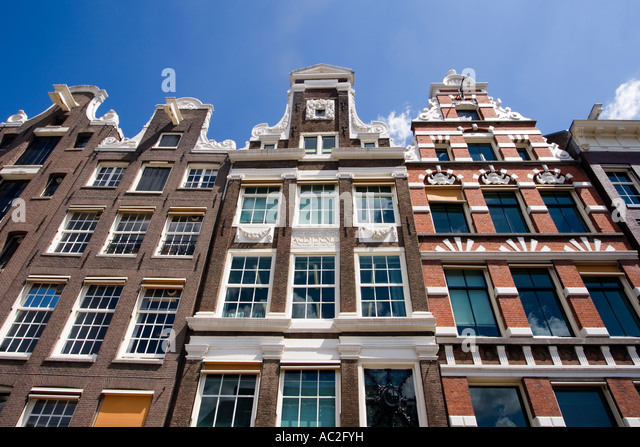 Amsterdam Damrak traditional architecture canalside houses - Stock Image