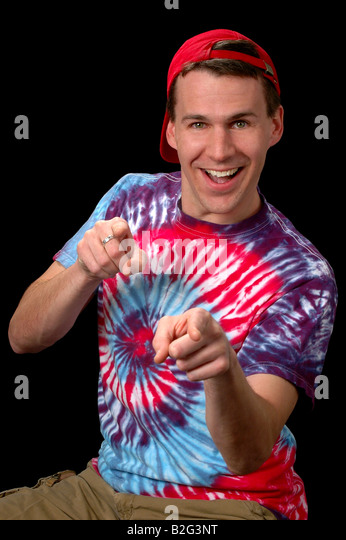 Cool Guy pointing over dark background - Stock Image