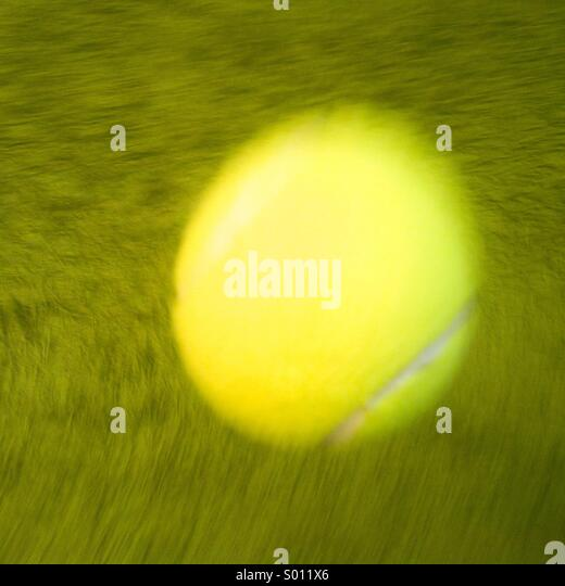 Moving tennis ball on Grass Court - Stock Image