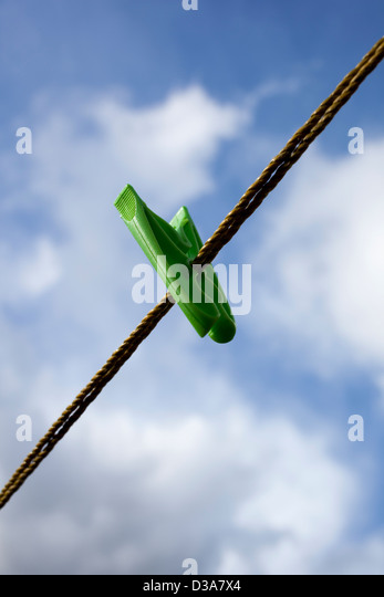 A single green clothes peg or pin on a washing line, against a cloudy blue sky. - Stock-Bilder
