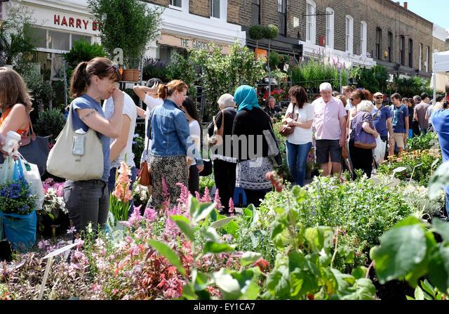 people walking in Colombia Road flower market. - Stock Image