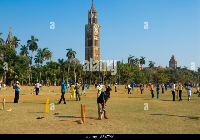 People playing cricket at the Oval Maiden with the Clock Tower in the background Mumbai India - Stock Image
