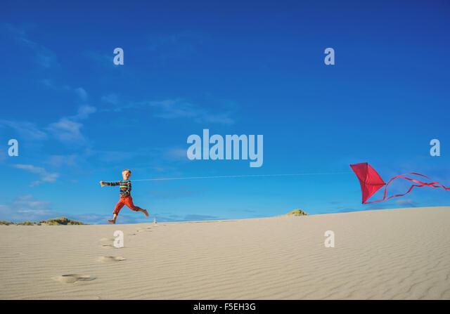 Boy flying red kite on sandy beach - Stock Image