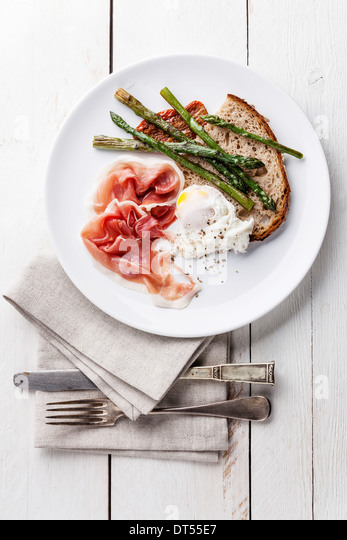 Breakfast with poached egg, parma and asparagus on white wooden background - Stock Image