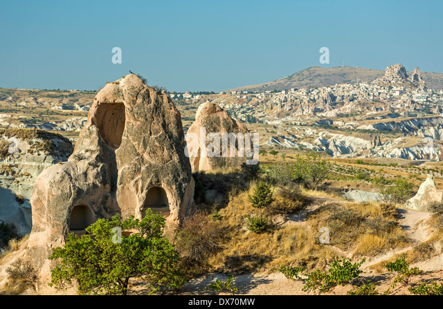 Dwellings in fairy chimneys and Uchisar (R) in distance, Red Valley, Cappadocia, Turkey - Stock Image