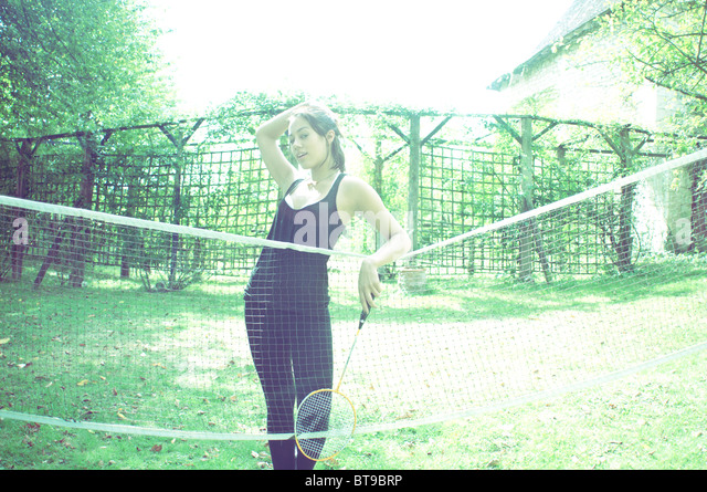 A young woman standing at a badminton net - Stock Image