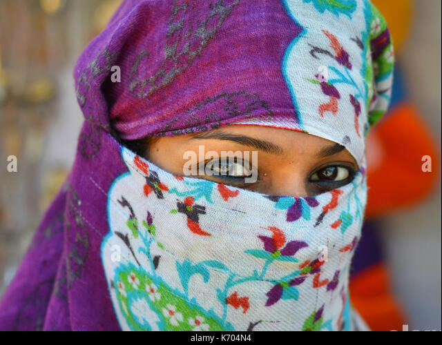 Young Indian woman with very beautiful eyes, covering her hair and face with a trendy secular headscarf; Junagadh, - Stock Image