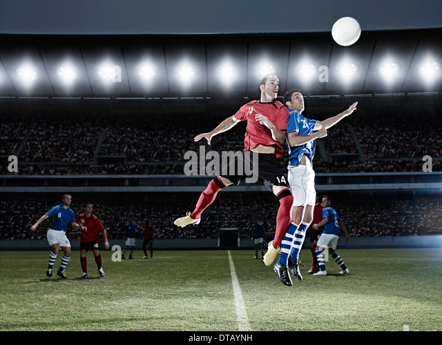 Soccer players jumping for ball on field - Stock-Bilder