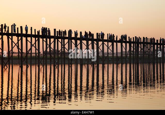 Sunset silhouettes at U Bein Bridge across the Taungthaman Lake in Amarapura, Myanmar (Burma) - Stock-Bilder
