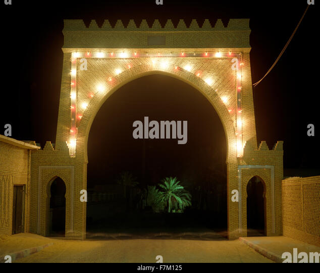 A lighted gate at night leads to the main Palmeraie in Tozeur. A palm tree is illuminated in the distance. Tozeur, - Stock Image