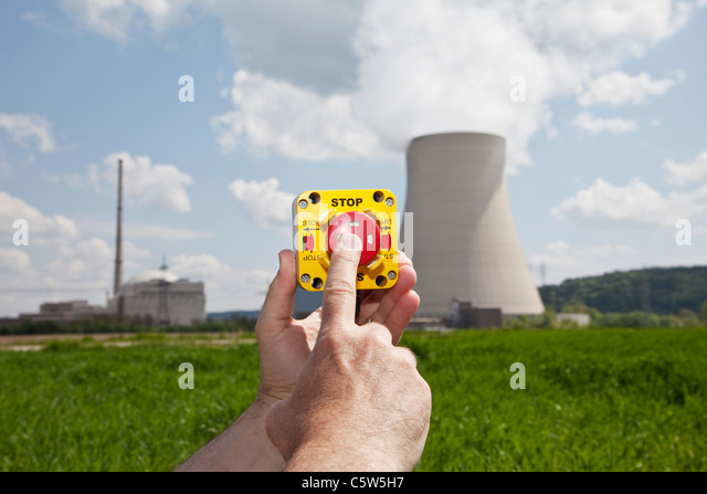 Germany, Bavaria, Unterahrain, Hand of man pressing shut off button near AKW Isar - Stock Image