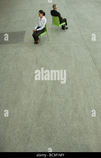 Businesswoman and businessman sitting back to back, high angle view, full length - Stock Image